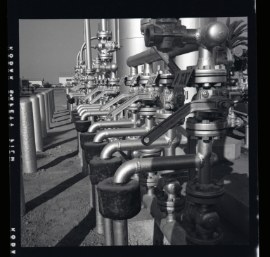 """Long Beach Harbor lease to Richfield. Along the west side of the Los Angeles River flood channel. A very consecrated production site. All pumps were underground and the """"silver tanks"""" (sic) separators from oil & gas. 1946-48 period of harbor oil production and subsidence. (2 of 3)"""