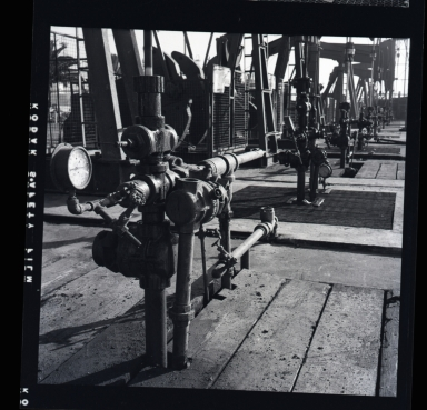 "Long Beach Harbor lease to Richfield. Along the west side of the Los Angeles River flood channel. A very consecrated production site. All pumps were underground and the ""silver tanks"" (sic) separators from oil & gas. 1946-48 period of harbor oil production and subsidence. (3 of 3)"