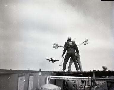 "Aircraft carrier ""Valley Forge"" in operation.  Landing Signal Officer guides a plane landing on flight deck. (April 27)"