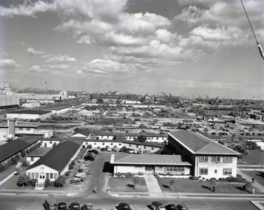 """A two-picture panorama photo of the Long Beach Naval Station and Shipyard. (Two same-size photo prints will match at the overlap of the white house with the number """"2"""" on the wall under second-story window)."""