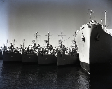 """""""The Nineteenth Fleet"""" (aka, """"The Zippered Fleet"""") was a collection of """"mothballed"""" ships at U.S. Navy Shipyard. The smaller ships shown are attack destroyers that have been cleaned, their hulls painted with anti-fouling paint and their armaments covered with a cocoon to protect from dampness, and dehydration equipment installed. The larger ship is the """"Isle Royal"""", a submarine tender which carries small stores, food and movies to supplement stores on subs."""