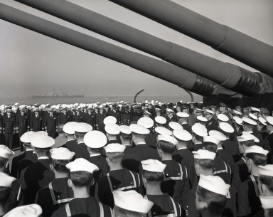 "Change of command and retirement of U.S. Admiral William F. Halsey on board battleship South Dakota. Ship's company assembled on afterdeck for the ceremony honoring ""Bull"" Halsey, winner of the battle of the Pacific during WW II fight with Japan. The ship's 12-inch guns are above the company. (November 22, Thanksgiving Day)"