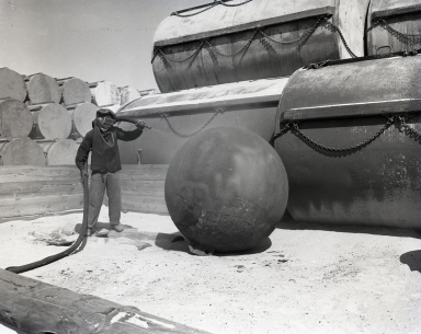 Sandblasting a steel sphere at the U.S. Naval Ammunition & Net Depot. The sphere and the large closed cylinders were part of a giant submarine defense net that was strung across Long Beach and Los Angeles harbors during WWII to protect shipping and the U.S. Navy from foreign submarine attack. After the war, the net was cleaned and stored at Seal Beach.