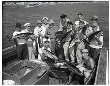 A group of fishermen displaying their catch of albacore.