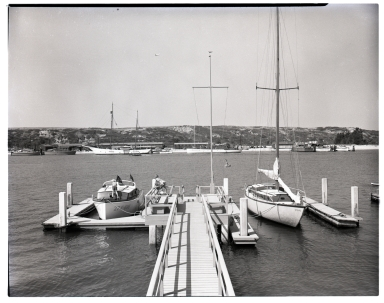 A view from the base of a dock with two boats tied up.  In the distance are two yachts.
