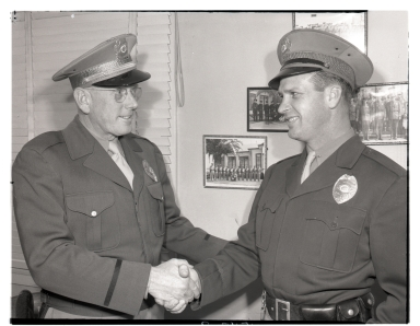 A Newport Beach police officers congratulating another.