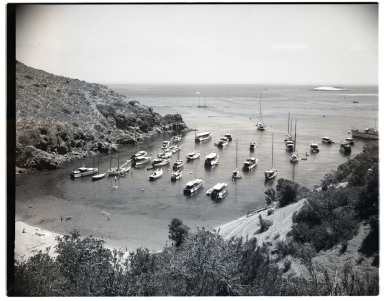 Boats anchored in a cove, with swimming beach.  Possible Two Harbors, Santa Catalina Island.