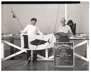 John Loth with Capt. Eddie Offerle holding a flag to anounce he caught the first Bluefin Tuna of the season.