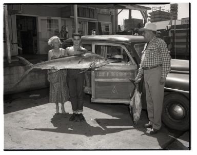Man holding a marlin. He is standing in front of a car with Twin Pines Ranch stenciled on the door.  A woman poses next to him as a man watches from the right.