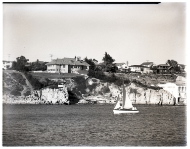 Hole House and Kerckhoff Lab viewed from the end of the Balboa Peninsula.  A sailboat appears in the the foreground.