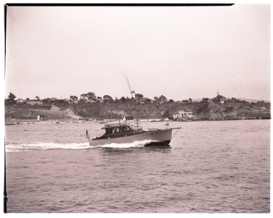 Motorboat (27 E 569) cruising by China Cove in Newport Harbor.  The China House is in the background.