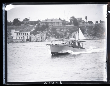 Motorboat (27 E 569) cruising by China Cove in Newport Harbor.  The Kerckhoff Marine Laboratory is in the background.