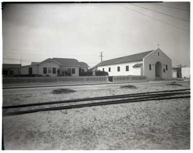 View of an unidentified church by railroad tracks.