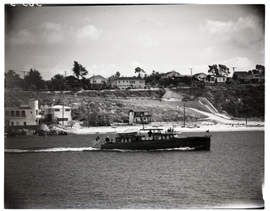 Powerboat crusing past China Cove toward the exit of Newport Harbor.  The Kerckhoff Marine Laboratory is to the left.