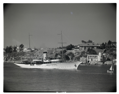Large yacht <i>Vida</i> passing by China Cove while exiting Newport Harbor.  The Kerckhoff Marine Laboratory and Hole house appear in the background.