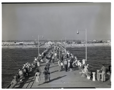 The Newport pier crowded with people fishing a walking.
