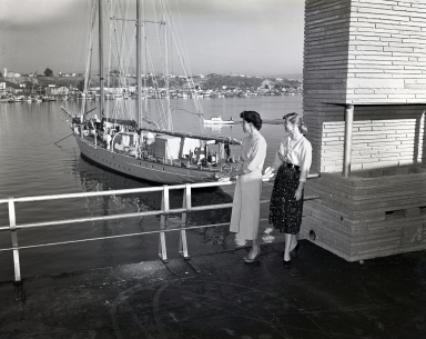 Two secretaries looking out from the 2nd floor deck of the Newport Balboa Savings and Loan building in Lido Village.  The yacht Pioneer is in the background.