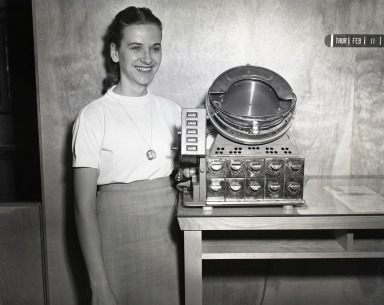 Newport Balboa Savings and Loan employee with a coin sorting machine.