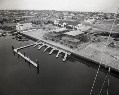 View of the Newport Balboa Savings and Loan building and Lido Shopping Center from the mast of the yacht Pioneer.