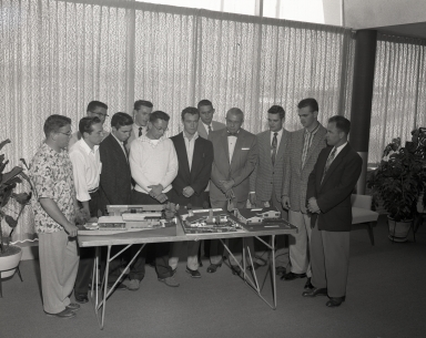 Paul Palmer with architect students review architectural models of homes.