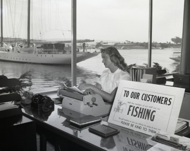 """""""Didn't go fishing."""" Employee of Newport Balboa Savings and Loan looking forlorn as she sits next to a sign that reads """"TO OUR CUSTOMERS, Half the members of our staff are . . . FISHING. The staff members on dury are suffering the pangs of envy, PLEASE BE KIND TO THEM!"""" The yacht Pioneer is anchored in the background."""
