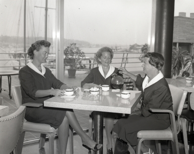 Newport Balboa Savings and Loan employees at a table drinking coffee.