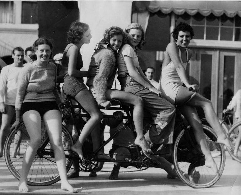 Young women posing on a 2-person bicycle.