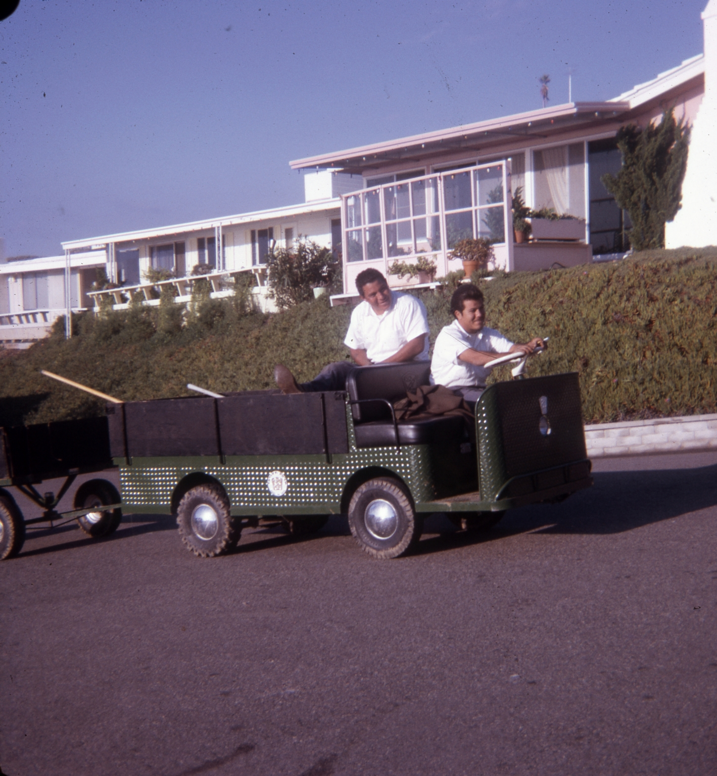 Two employees of the Dana Strand Club in an electric cart, with a residence in the background.