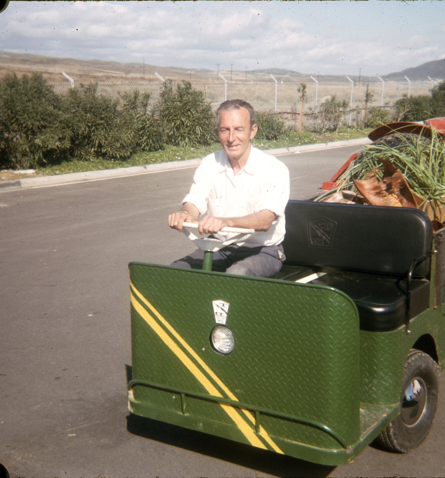 A employee of the Dana Strand Club sitting behind the wheel of an electric cart.