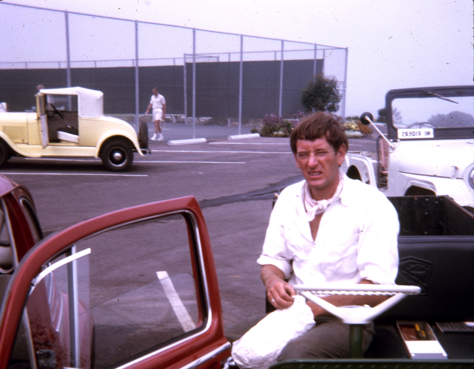 A man sitting behind the wheel of an electric cart.  The tennis court appears in the background.