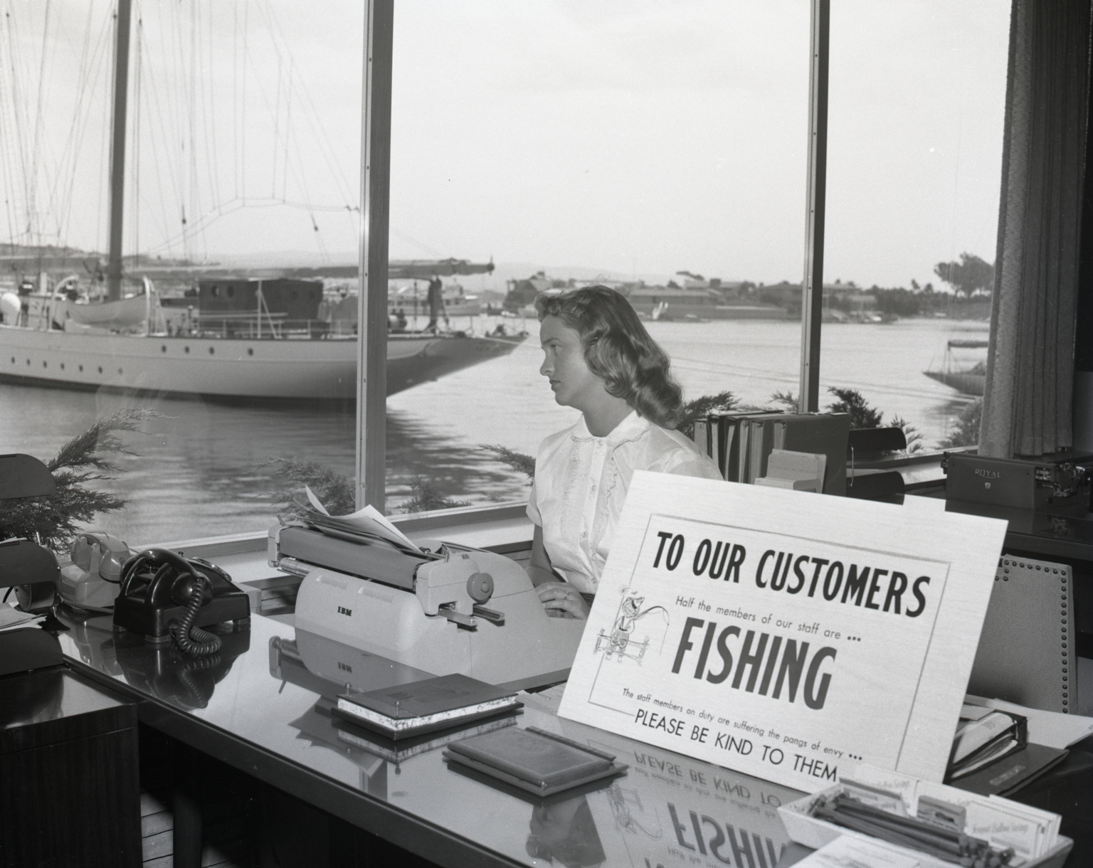 """Didn't go fishing."" Employee of Newport Balboa Savings and Loan looking forlorn as she sits next to a sign that reads ""TO OUR CUSTOMERS, Half the members of our staff are . . . FISHING. The staff members on dury are suffering the pangs of envy, PLEASE BE KIND TO THEM!"" The yacht Pioneer is anchored in the background."